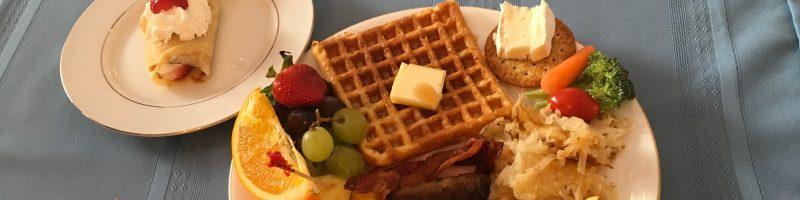 brunch, waffles, crepe, hash browns, bacon, grapes, strawberries, orange slice